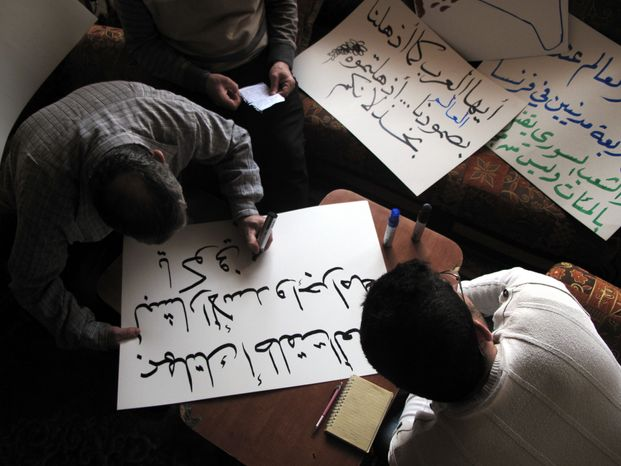 Syrian activists prepare signs for upcoming protests at a house in Damascus, Syria, on April 3, 2012. Syrian activists say there have been explosions and clashes in several parts of the country even as the government claims it has started to withdraw troops from some cities in compliance with an international cease-fire plan. (Associated Press)