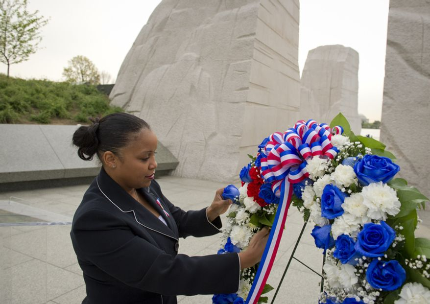 DeAndra Johnson Cullen Special Assistant Fair Housing and Equal Opportunity, U.S. Department of Housing and Urban Development (HUD), replaces a fallen rose on the wreath as people prepare for the Fair Housing Month 2012 Wreath-Laying Ceremony for the 44th anniversary of the 1968 assassination of Dr. Martin Luther King, Jr.  (Rod Lamkey Jr/The Washington Times)