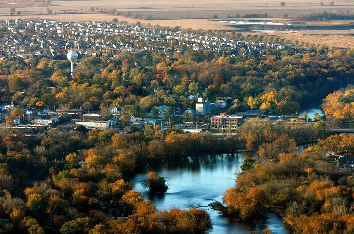 ** FILE ** This Oct. 2010 aerial file photo shows the Fox River as it flows into downtown Oswego, Ill., in Kendall County, with subdivisions and farmland to the southeast. The nation's No. 1 fastest-growing county from 2000 to 2010, Kendall was part of an exurban wave in the heady 2000s that more than doubled its population. But Census estimates as of July 2011 highlight a shift in population trends, following an extended housing bust and renewed spike in oil prices: outlying suburbs are now seeing their growth fizzle to historic lows, halting American city dwellers' decades-long exodus to sprawling homes in distant towns. (AP Photo/The Beacon-News, Marianne Mather, File)