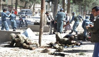 Wounded U.S. soldiers lie on the ground at the scene of a suicide attack in Maimanah, the capital of Faryab province, north of Kabul, Afghanistan, on Wednesday, April 4, 2012. (AP Photo/Gul Buddin Elham)