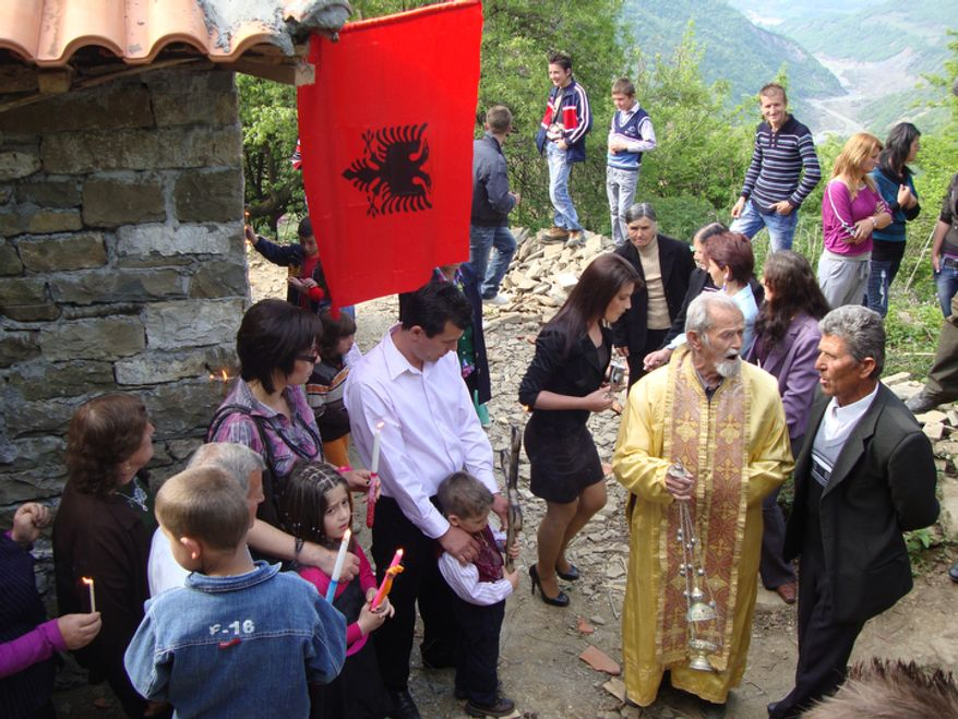 An Easter parade commences around the town church in Selta, a village in the Shpati region of central Albania. The lay priest (in yellow) sings old hymns with shepherd Anastas Karaj. A migrant worker from Greece (standing under flag) bought the processional cross for his son at an auction. (Eckehard Pistrick/Special to The Washington Times)