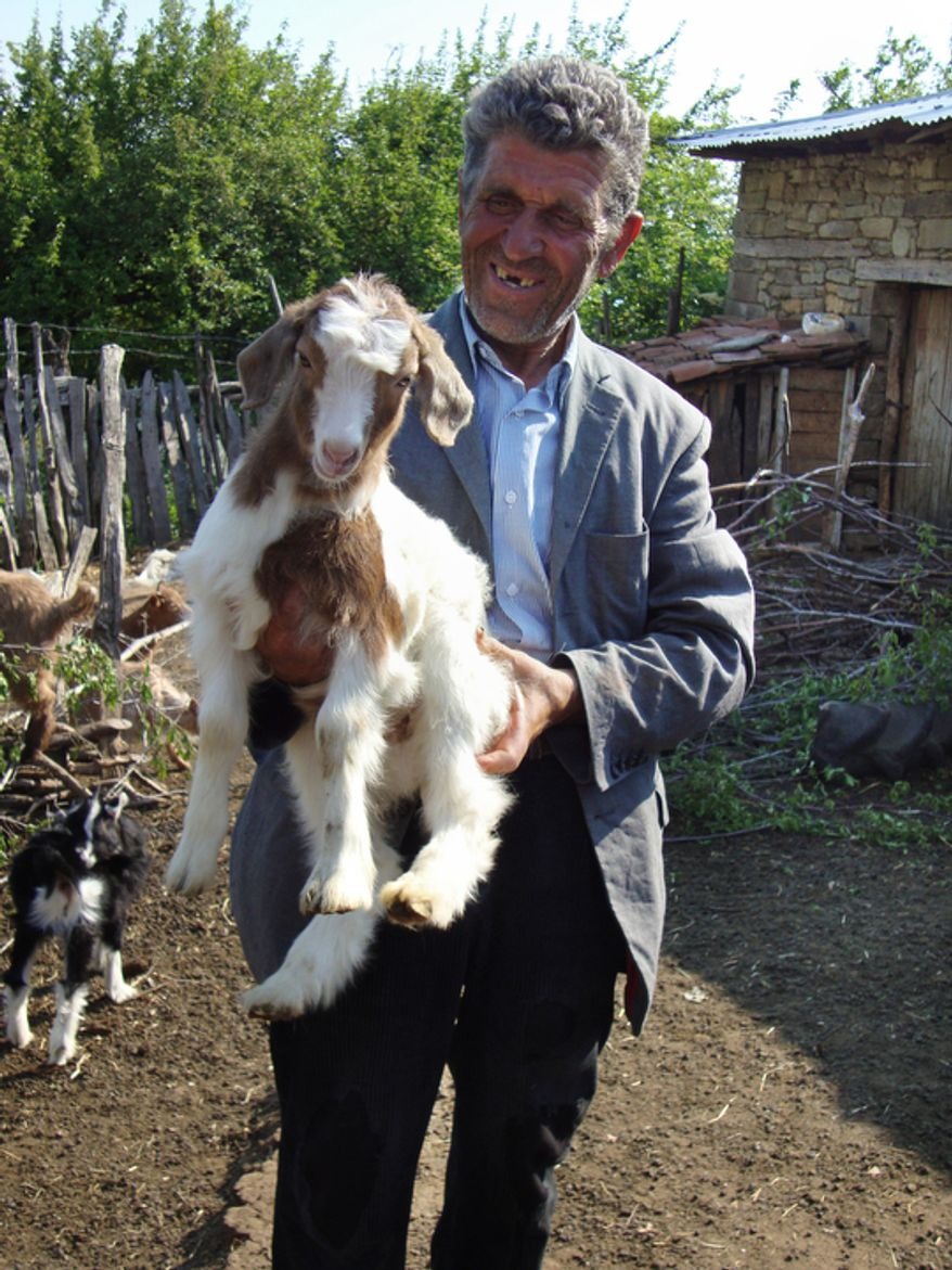 Anastas Karaj, a shepherd from the village of Selta in central Albania, holds his favorite goat in front of its stall. (Eckehard Pistrick/Special to The Washington Times)