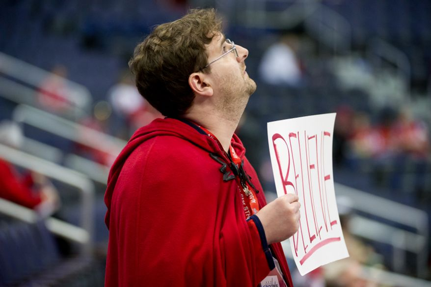 "Capitals fan Trevor White of Silver Spring, Md. wears a red cape and holds a poster that reads ""Believe"" during warmups as the Washington Capitals take on the Florida Panthers in National Hockey League hockey at the Verizon Center, Washington, D.C., Thursday, April 5, 2012. (Andrew Harnik/The Washington Times)"