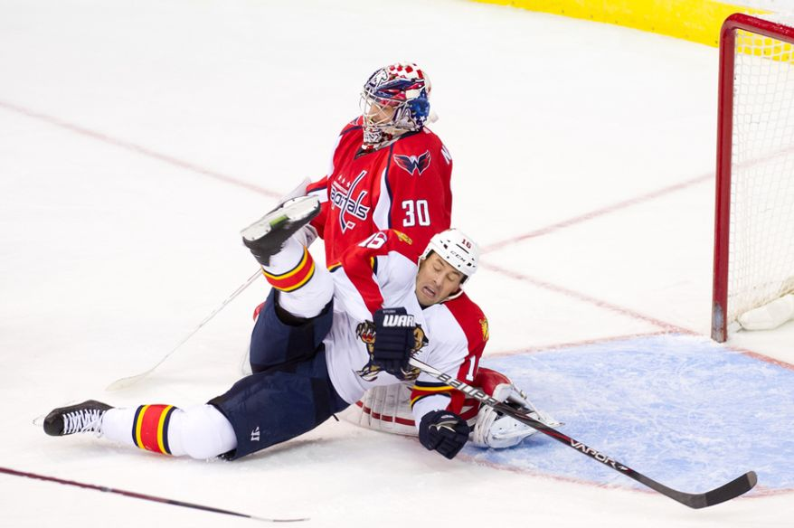 Washington Capitals goalie Michal Neuvirth leaves the game after being injured when Florida Panthers left wing Marco Sturm crashes into him in the second period in Washington on Thursday, April 5, 2012. (Andrew Harnik/The Washington Times)
