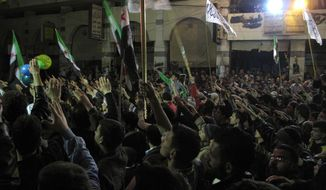 In this Wednesday, April 4, 2012, photo, Syrians raise their hands vowing to continue fighting until President Bashar Assad's regime falls during a protest in a neighborhood in Damascus, Syria. (AP Photo)