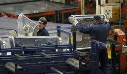 Auto workers stack the inner door panel for the Ford Explorer on April 4, 2012, at the Ford Stamping Plant in Chicago Heights, Ill. (Associated Press)