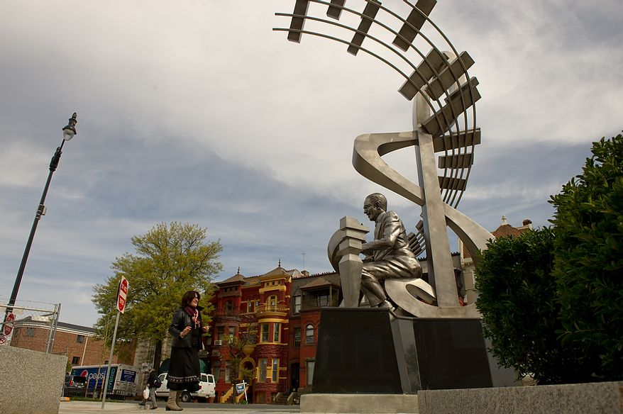 Gena Biganzoli of Tulum, Italy, left, checks out a newly installed stainless steel statue of D.C. native and jazz legend Duke Ellington in front of the redesigned historic Howard Theatre which is set to reopen with a ribbon cutting Monday and an opening night gala on Thursday, Washington, D.C., Thursday, April 5, 2012. (Andrew Harnik/The Washington Times)