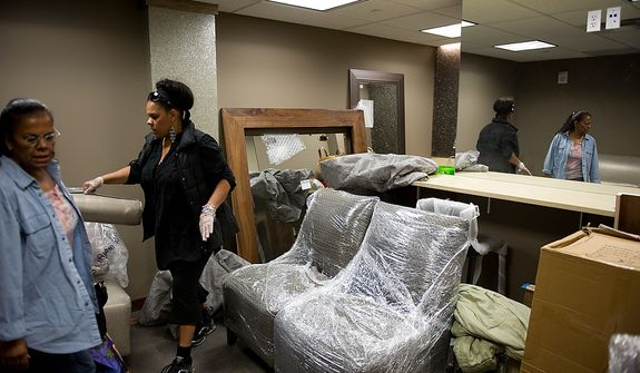 Sofalé Ellis, owner of Sofalé Artistic Designs, second from left, and her mother Phyllis Ellis of Glendale, Md., left, set up the downstairs green room of the redesigned historic Howard Theatre which is set to reopen with a ribbon cutting Monday and an opening night gala on Thursday, Washington, D.C., Thursday, April 5, 2012. (Andrew Harnik/The Washington Times)
