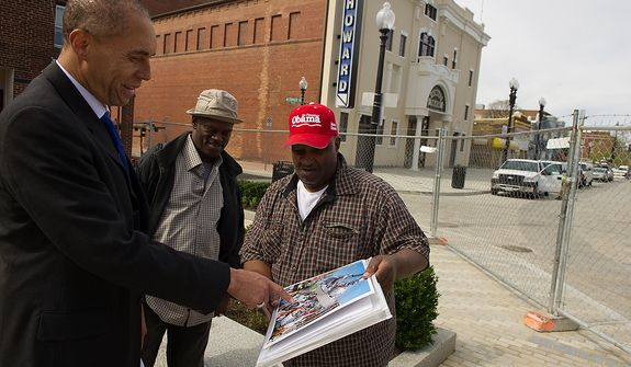 Thomas A. Hart, Jr., a local property owner, left, and Michael Hood of Washington, D.C., second from left, looks at Charles Ramsey's poster design of a newly installed stainless steel statue of D.C. native and jazz legend Duke Ellington with music legends super imposed into it while outside the redesigned historic Howard Theatre which is set to reopen with a ribbon cutting Monday and an opening night gala on Thursday, Washington, D.C., Thursday, April 5, 2012. (Andrew Harnik/The Washington Times)