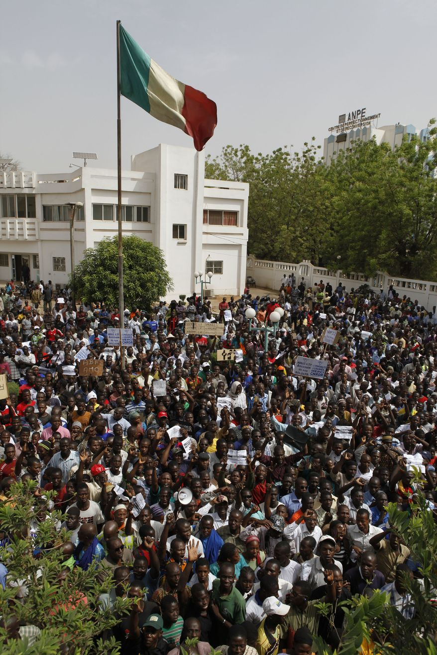 **FILE** People wait for coup leader Capt. Amadou Haya Sanogo to make an appearance March 28, 2012, at the office of the Prime Minister in Bamako, Mali, as thousands rallied in a show of support for the recent military coup. (Associated Press)