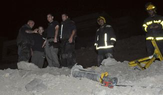 Israeli police stand next to a rocket that landed in the resort town of Eilat in southern Israel, early April 5, 2012. At least one rocket hit Eilat near the Egyptian and Jordanian borders, Israeli police said, causing no injuries. A police spokesperson said the rocket was likely launched from Egypt's Sinai Peninsula. (Associated Press)