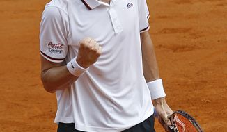 U.S. team player John Isner reacts after winning his match against France's Gilles Simon in the quarterfinal of the Davis Cup between France and U.S. in Monaco on Friday, April 6, 2012.(AP Photo/Remy de la Mauviniere)