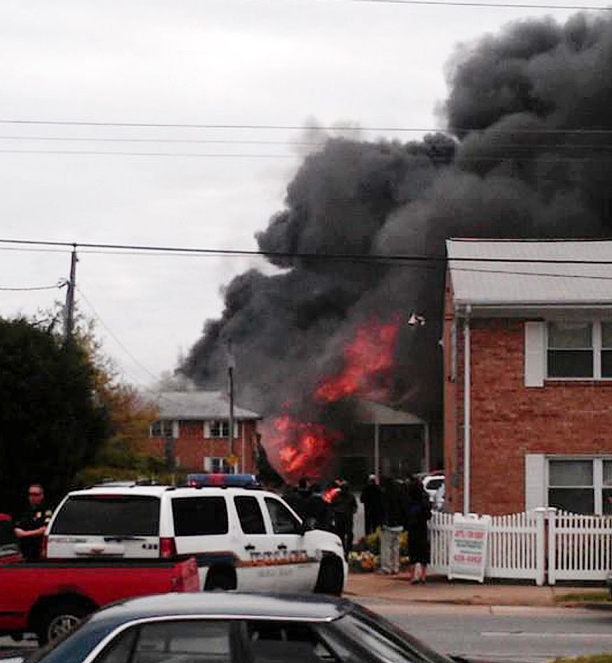 In this image made from video and provided by WVEC-TV, smoke billows near an apartment complex where a Navy jet crashed in Virginia Beach, Va., on April 6, 2012. The F/A-18 Hornet crashed into the apartment building, officials said, and the two-member crew ejected safely. There were no immediate reports of injuries on the ground. (Associated Press/WVEC-TV)