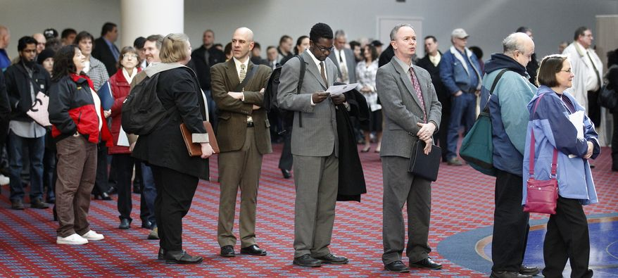 **FILE** Job seekers stand in line March 7, 2012, during the Career Expo job fair in Portland, Ore. (Associated Press)