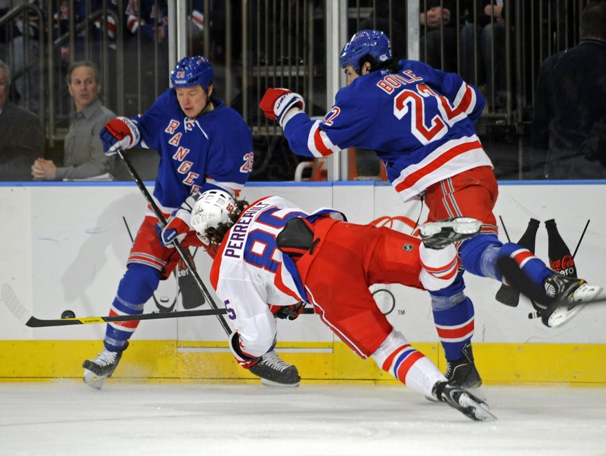 Washington Capitals' Mathieu Perreault (85) is sent flying on a check by New York Rangers' Brian Boyle, right, as Rangers Ruslan Fedotenko, of Ukraine, looks on during the first period of an NHL hockey game Saturday, April 7, 2012, at Madison Square Garden in New York. (AP Photo/Bill Kostroun)
