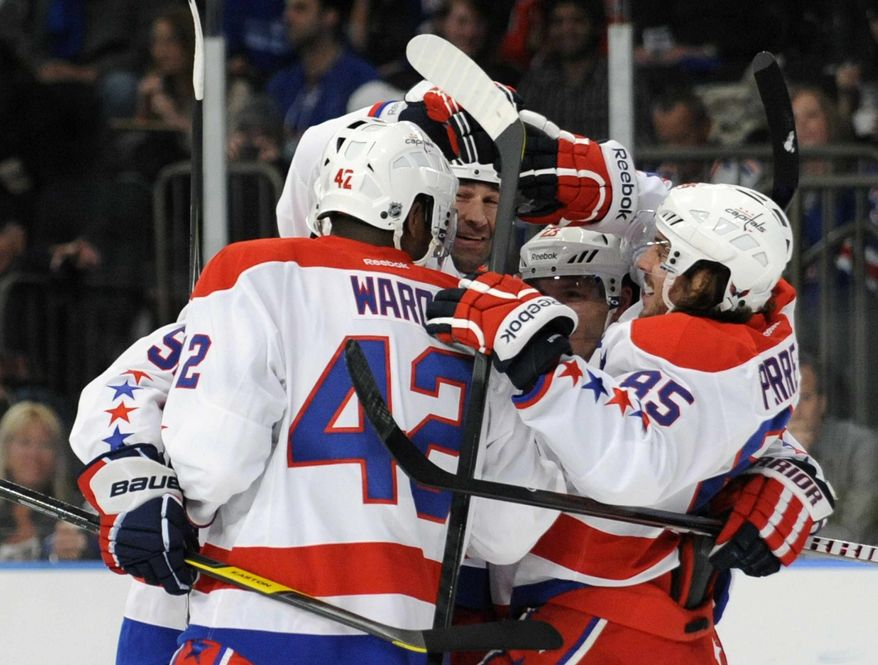 Washington Capitals' Mathieu Perreault, right, celebrates his goal with teammates during the first period of an NHL hockey game against the New York Rangers, Saturday, April 7, 2012, at Madison Square Garden in New York. (AP Photo/Bill Kostroun)