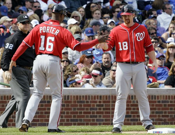 Washington Nationals' Chad Tracy, right, celebrates with third base coach Bo Porter at third during the eighth inning of a baseball game against the Chicago Cubs in Chicago, Saturday, April 7, 2012. (AP Photo/Nam Y. Huh)