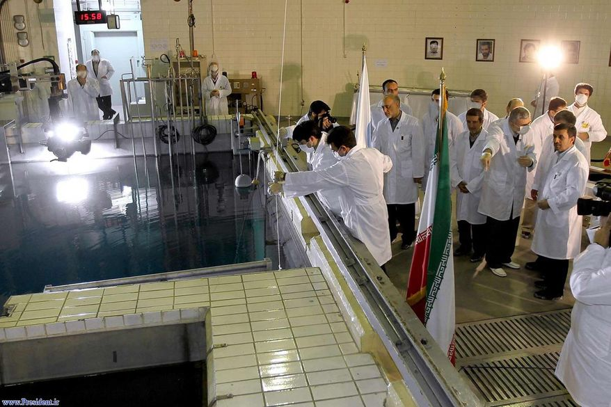 ** FILE ** In this Feb. 15, 2012, file photo, provided by the Iranian President's Office, Iranian President Mahmoud Ahmadinejad, right, is escorted by technicians during a tour of Tehran's research reactor center in northern Tehran, Iran. (AP Photo/Iranian President's Office, File)