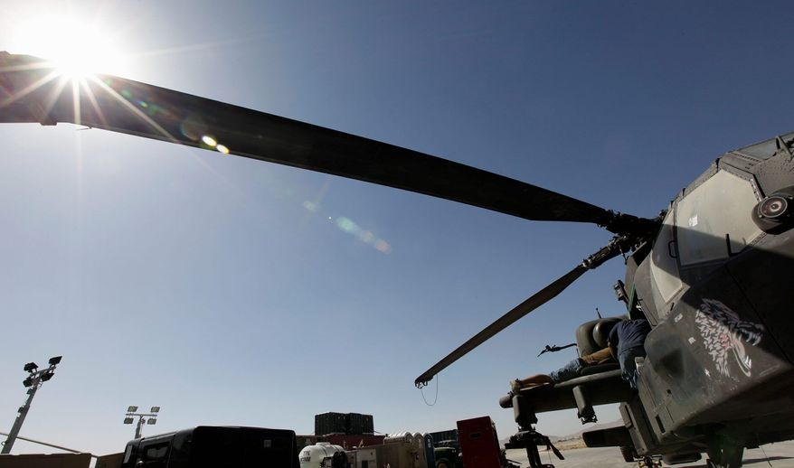 **FILE** Two civilian contractors (right) in 2009 work on an AH-64 Apache helicopter in Afghanistan. (Associated Press)