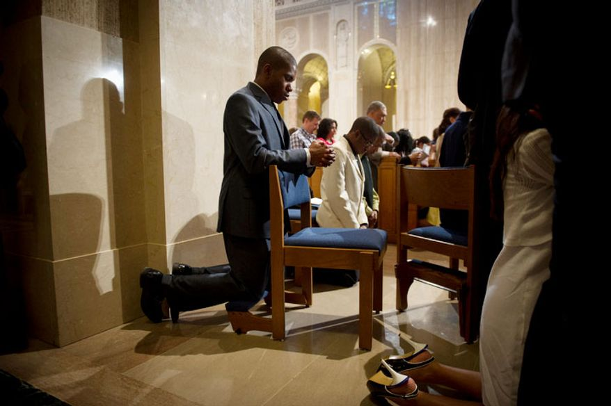 Hilary Unaegbu, of Bowie, Md., kneels near the aisles during a prayer, at the Basilica of the National Shrine of the Immaculate Conception. (Rod Lamkey Jr/The Washington Times)