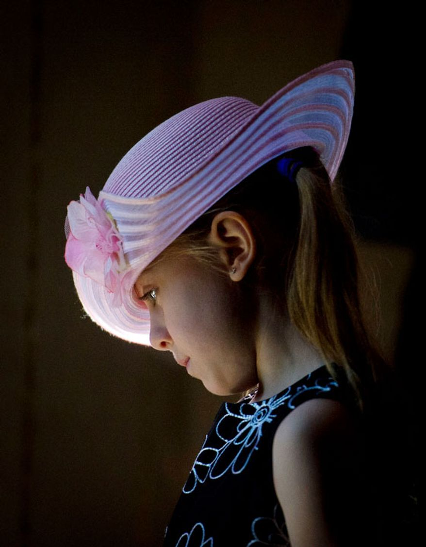 Abigail Lickteig, 6, of Stafford, Va., waits to leave with her family following Easter Sunday Mass at the Basilica of the National Shrine of the Immaculate Conception. (Rod Lamkey Jr/The Washington Times)