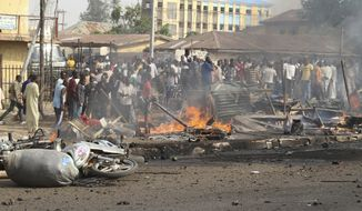 Onlookers gather at the site of a bomb explosion on a road in Kaduna, Nigeria, on Sunday, April 8, 2012. Diplomats had warned of possible terrorist attacks over the Easter holiday, police said. (AP Photos/Emma Kayode)