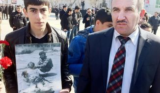 Aloysat Gasimov (right) was one of the first Azeri officials to reach the scene of the massacre in Khojaly 20 years ago. The student beside him holds a photo of Mr. Gasimov, now the head of a cultural center near the site of the 1992 massacre, kneeling next to a victim. (Eric J. Lyman/Special to The Washington Times)