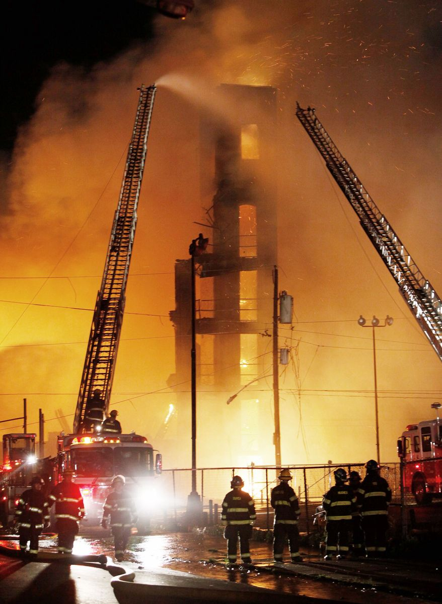 Flames pour from the windows of an abandoned warehouse in Philadelphia as crews douse it with water from all sides. Hot embers from the main fire blew to nearby structures, causing small fires that damaged six homes. (Associated Press)