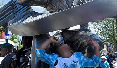 """Arisemma Okrah, 5, drinks a soft drink while playing on the sculpture of Duke Ellington outside the newly renovated Howard Theatre at Monday's """"community day."""" (Barbara L. Sallisbury/The Washington Times)"""