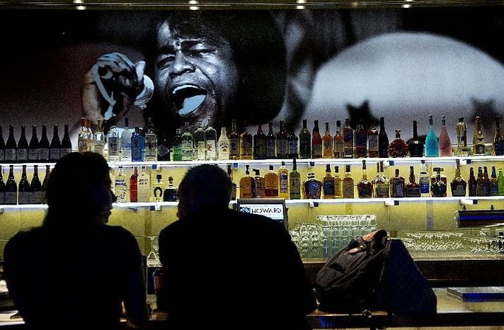 A woman and man chat at the bar in front of a picture of James Brown at the newly renovated Howard Theatre in Northwest at its grand opening Monday. The space is filled with photographs of famous acts that once played there, including Ella Fitzgerald, D.C.&am