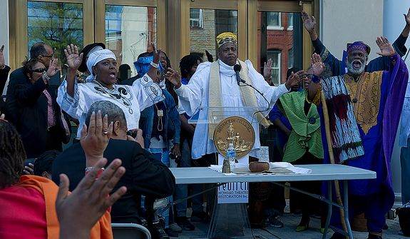 Melvin Deal, center, in white, founding director of the African Heritage Dancers and Drummers, leads the crowd in a libation, an offering of water and acknowledgement to the ancestors, at the grand opening of the newly renovated Howard Theatre in Washington, D.C. on Monday, April 9, 2012. (Barbara L. Salisbury/The Washington Times)
