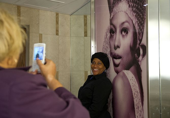 Lipia Gereau, who says she loves Diana Ross, has her picture taken with a huge likeness of the star inside the women's restroom at the newly renovated Howard Theatre in Washington, D.C., on Monday, April 9, 2012. (Barbara L. Salisbury/The Washington Times)