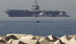 ** FILE ** A small boat passes in front of the U.S. Navy aircraft carrier Enterprise, anchored off the coast of Faliro, Greece, near Athens, on Thursday, March 29, 2012. (AP Photo/Petros Giannakouris, File)