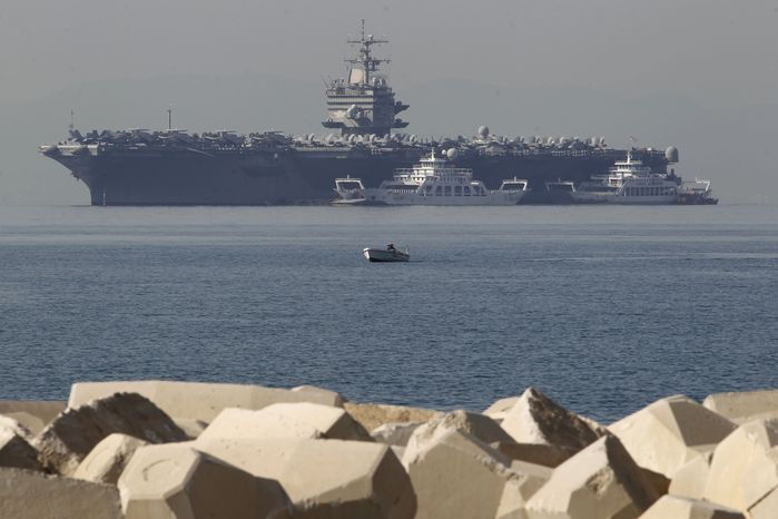 ** FILE ** A small boat passes in front of the U.S. Navy aircraft carrier Enterprise, anchored off the coast of Faliro, Greece, near Athens, on Thursday, March 29, 2012. (AP Photo/Petro