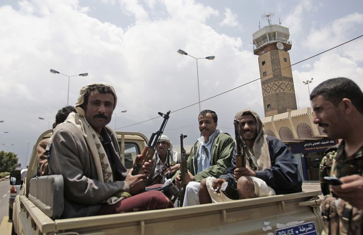 Yemeni policemen sit in a pickup truck in front of the international airport in Sanaa, Yemen, on Sunday, April 8, 2012. The airport reopened Sunday, a day after gunmen loyal to the nation's former president seized the facility, officials said. (AP Photo/Hani Mohammed)