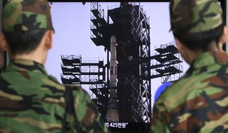 South Korean soldiers at a Seoul train station watch a TV news program showing North Korea's Unha-3 rocket on Monday, April 9, 2012. (AP Photo/Ahn Young-joon)