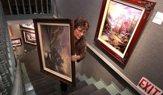 "Denice Gould, who works at the Thomas Kinkade Gallery in Placerville, Calif., moves one of the artist's works Monday. Demand has skyrocketed since the ""Painter of Light"" died Friday. The gallery got 300 online orders in 48 hours. (Associated Press)"