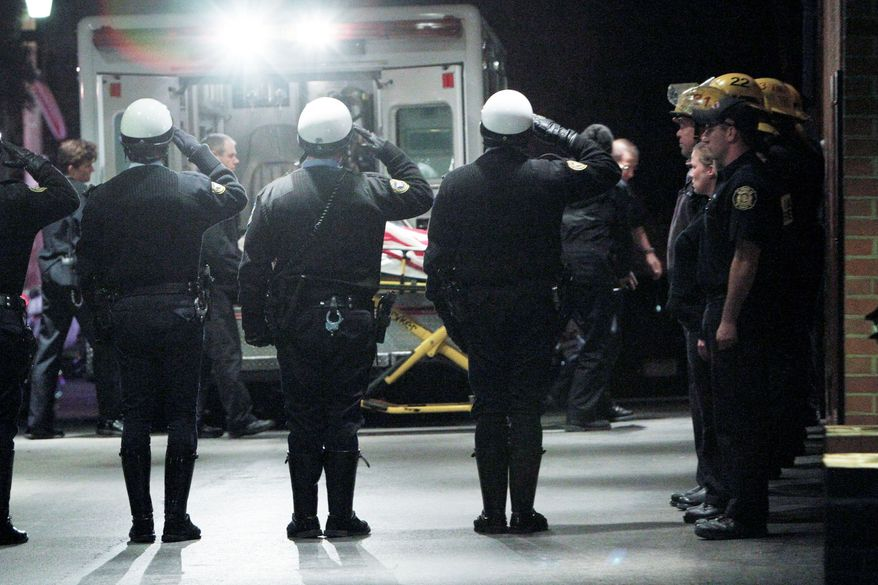 ASSOCIATED PRESS Police officers salute as the body of firefighter Lt. Robert Neary is transferred early Monday to a funeral home in Philadelphia. The lieutenant, 60, was a 37-year fire department veteran. He was killed battling a blaze at an abandoned warehouse.