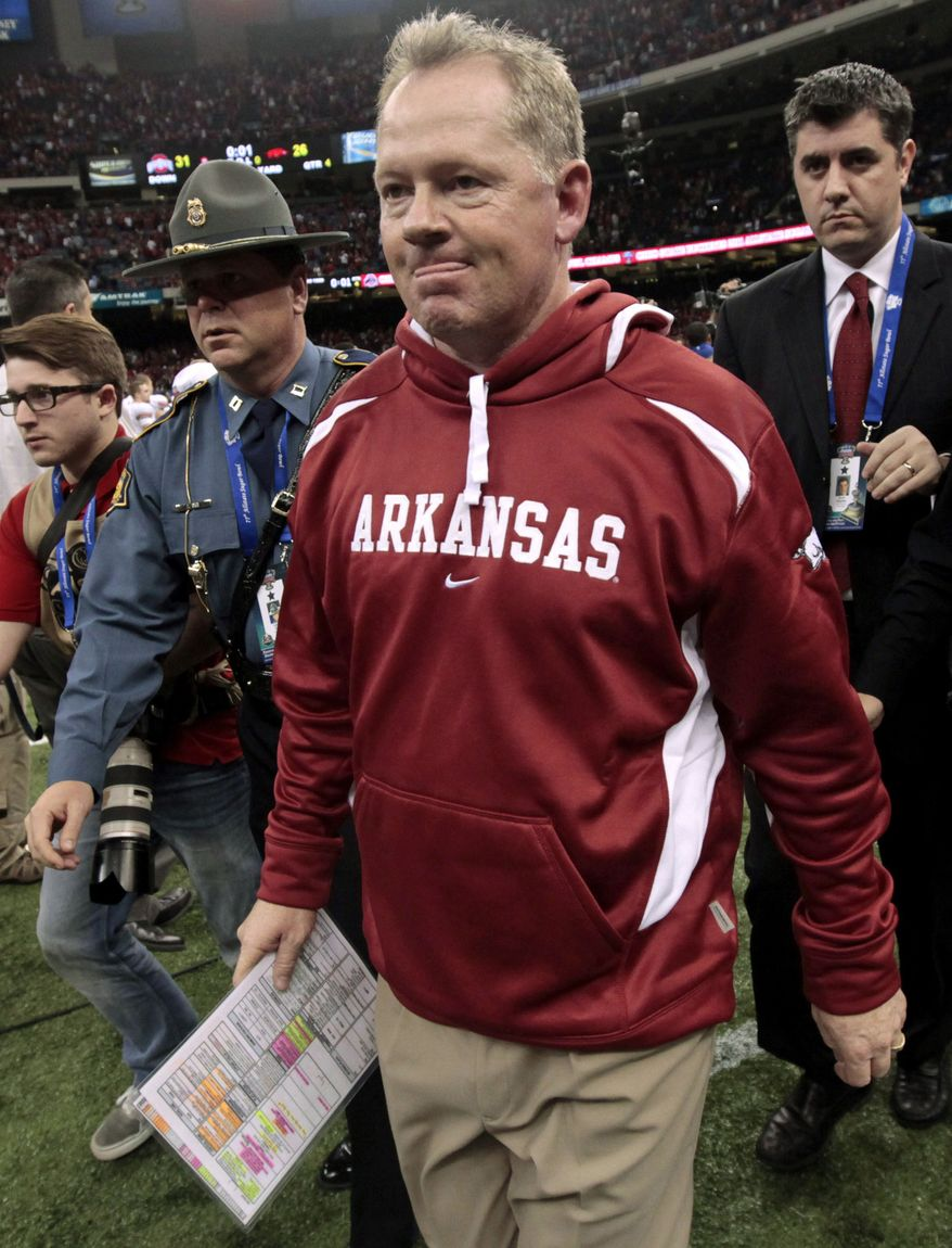 FILE - In this Jan. 4, 2011, file photo, Arkansas coach Bobby Petrino, followed by his security detail Arkansas State Police Captain Lance King, left, walks of the field after Arkansas' 31-26 loss to Ohio State in the Sugar Bowl NCAA college football game at the Louisiana Superdome in New Orleans. The Arkansas State Police are taking another look at the motorcycle crash involving coach Petrino. Authorities say they want to know how State Police Captain Lance King wound up meeting Petrino after the crash at an intersection in Fayetteville. King, who provides security for the coach during the season, then drove Petrino to a hospital.(AP Photo/Gerald Herbert, File)