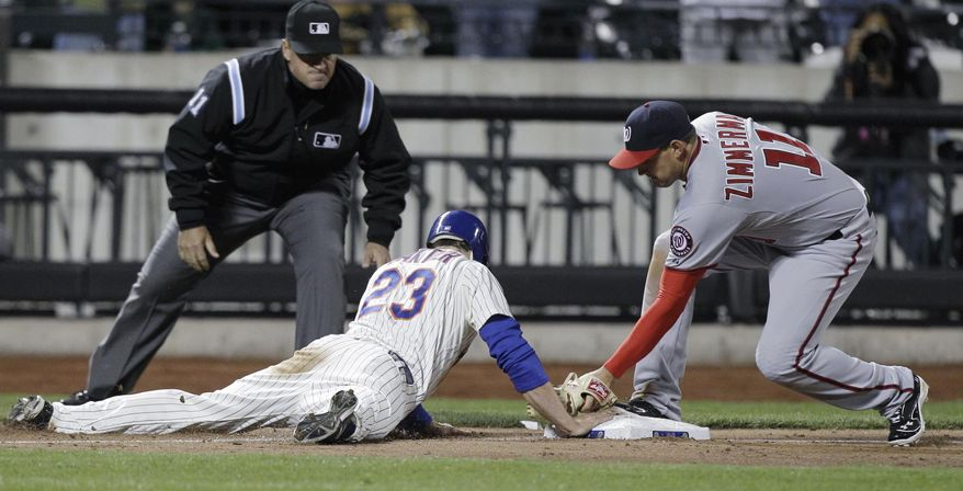 New York Mets' Mike Baxter is safe sliding back to third after advancing on Ruben Tejada's ninth-inning sacrifice bunt, as Washington Nationals third baseman Ryan Zimmerman applies a late tag and third base umpire Tony Randazzo watches in the Mets' 4-3 victory in a baseball game in New York, Monday, April 9, 2012. Baxter later scored on Daniel Murphy's single. (AP Photo/Kathy Willens)