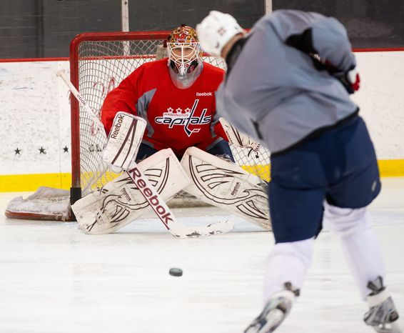 Braden Holtby, focusing on a shot by Jason Chimera during practice, has played in just seven NHL games this season. Drawing inspiraton from his mask, he will attempt to become the first rookie goalie to lead his team to a Stanley Cup title since Carolina's Cam Ward in 2006. (Andrew Harnik/The Washington Times)
