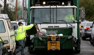 Waste Management Inc. collects garbage weekly for the city of Seattle. City officials are pondering a switch to every-other-week garbage collection and may test the concept at about 800 single-family homes in four areas this summer. (Associated Press)