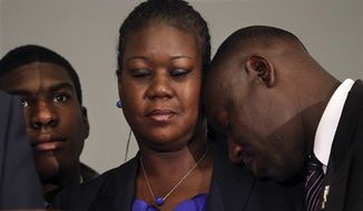 ** FILE ** Sybrina Fulton (center), the mother of Trayvon Martin, closes her eyes as the family attorney Benjamin Crump rests his head against her shoulder April 11, 2012, during a news conference at the Washington Convention Center in Washington about the arrest of George Zimmerman for the killing of Martin. To her right is her son, Jahvaris Fulton. (Associated Press)