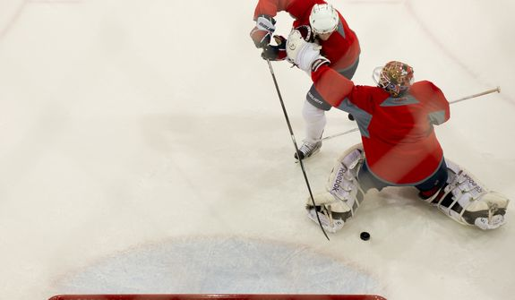 Washington Capitals center Brooks Laich (21), left, tries to score on Washington Capitals goalie Braden Holtby (70), right, during morning practice at Kettler Capitals Iceplex, Arlington, Va., Tuesday, April 10, 2012. (Andrew Harnik/The Washington Times)