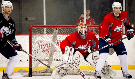 Washington Capitals goalie Braden Holtby (70), center, works out during morning practice at Kettler Capitals Iceplex, Arlington, Va., Tuesday, April 10, 2012. (Andrew Harnik/The Washington Times)