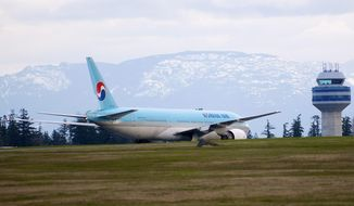 A Korean Air Boeing 777 is parked on the runway at Canadian Forces Base Comox on British Columbia's Vancouver Island after an emergency landing on Tuesday, April 10, 2012. (AP Photo/Canadian Press, Richard Warrington)