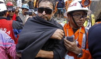 An unidentified miner (left) is helped by an emergency worker after being rescued from the Cabeza de Negro gold-and-copper mine in Yauca del Rosario, Peru, on Wednesday, April 11, 2012. Nine miners had been trapped inside the wildcat mine since Thursday. (AP Photo/Martin Mejia)