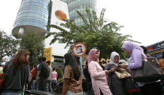 People wait as they are evacuated from a shopping mall after a strong earthquake was felt in Medan, Sumatra island, Indonesia, Wednesday, April 11, 2012. (AP Photo/Binsar Bakkara)