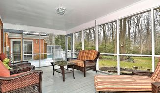A hallway off the kitchen leads to the screened porch, a three-season space with garden and nature views.