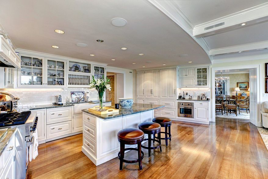 The kitchen in units 404 and 405 in Watergate South features granite counters, a center island with a breakfast bar, custom-designed cabinets and a coffered ceiling.